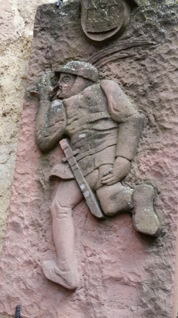 This plaque is on the left as you approach the tower entrance. It appears to be a soldier mooning and thumbing his nose to the enemy! We're thinking the Germans?  Couldn't find a date!